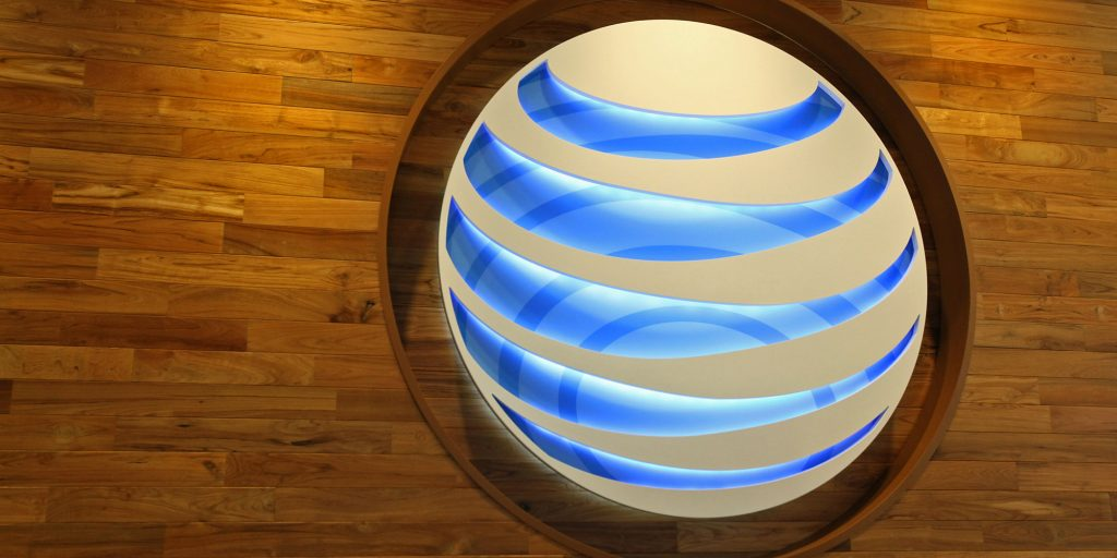 "An AT&T Inc. logo is displayed in the new AT&T Inc. store in Chicago, Illinois, U.S., on Thursday, Aug. 30, 2012. AT&T Inc. is refining its retail strategy with its first flagship store, a location on Chicago's Michigan Avenue that goes beyond phones and tablets to show services such as fitness applications and ""smartcar"" features. Photographer: Tim Boyle/Bloomberg via Getty Images"